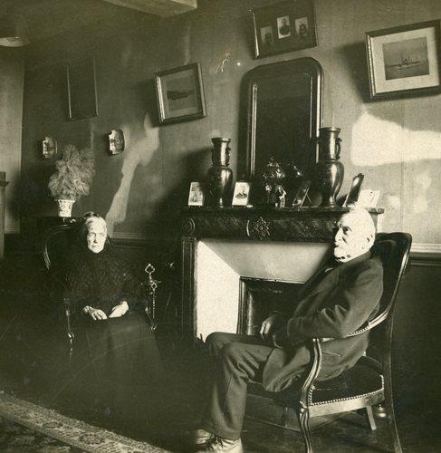 Photo du salon vers 1925, les peintures sont sous le papier peint, derrière le miroir et le tableau