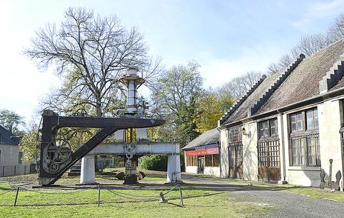 Marteau Pilon de 5 tonnes installé en 1886 dans l'Atelier des Grandes Forges   (fabrication des ancres à jas) et la Grue Calla datant de 1860 et restaurée en 2018. A droite l'entrée du musée